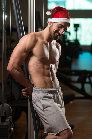 Portrait Of A Young Santa Claus Posing And Showing Bodybuilding Pose In Gym Stock Photo