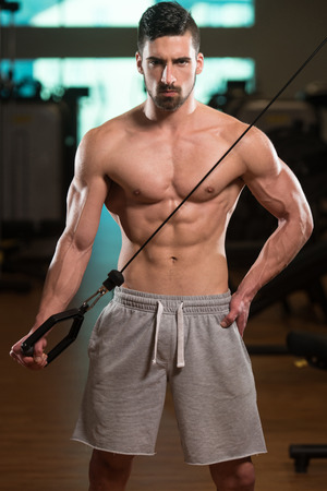 Young Muscular Fitness Bodybuilder Doing Heavy Weight Exercise For Triceps In The Gym Stock Photo