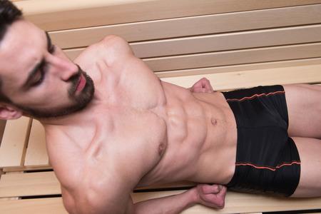 sauna nackt: Gl�cklich gut aussehend und attraktive junge Mann mit dem muskul�sen K�rper Entspannung im Hot Sauna