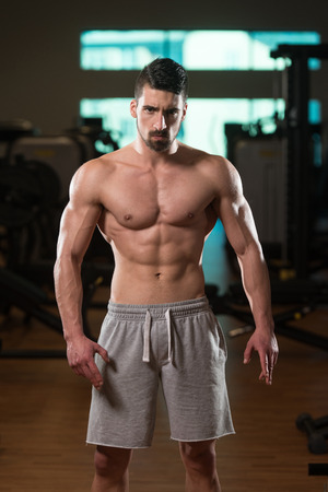 well build: Young Man Standing Strong In The Gym And Flexing Muscles - Muscular Athletic Bodybuilder Fitness Model Posing After Exercises Stock Photo