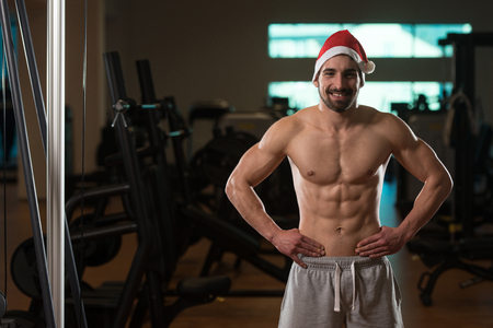 gym dress: Portrait Of A Young Santa Claus Posing And Showing Bodybuilding Pose In Gym Stock Photo