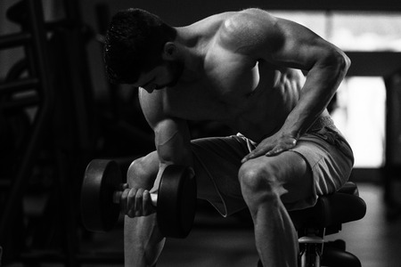 Young Muscular Man Doing Heavy Weight Exercise For Biceps With Dumbbells In Gym Stock Photo
