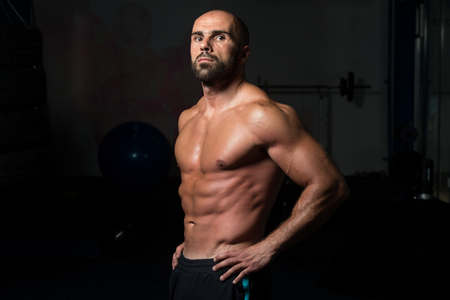 physically fit: Portrait Of A Physically Fit Man Showing His Well Trained Body In A Dark Room Stock Photo