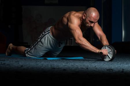 Fitnesstraining Junger Mann Fitness Workout für Bauch mit Toning-Rad