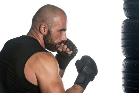 aggressiveness: Muscular Sports Guy Boxing Workout Over White Background Isolated - Boxer Is Hitting A Rubber