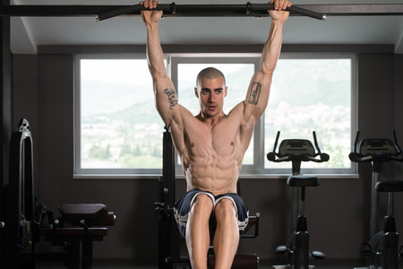 raises: Young Man Performing Hanging Leg Raises Exercise - One Of The Most Effective Ab Exercises