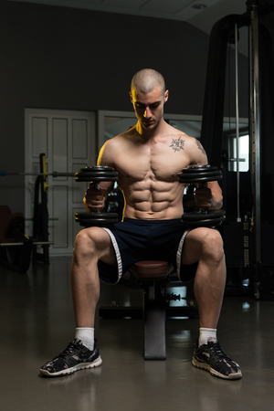 physically fit: Portrait Of A Physically Fit Young Man In A Healthy Club With Dumbbells Stock Photo