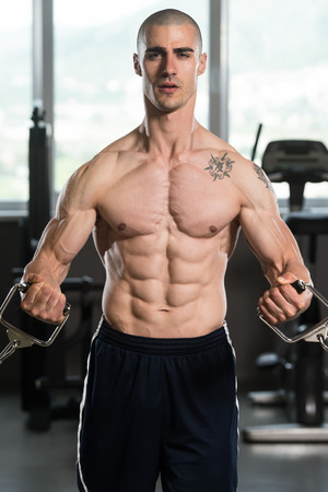 crossover: Young Bodybuilder Is Working On His Chest With Cable Crossover In Gym Stock Photo