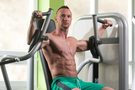 exercise machine: Butterfly Exercise Machine - Young Bodybuilder Doing Heavy Weight Exercise For Chest In The Gym Stock Photo