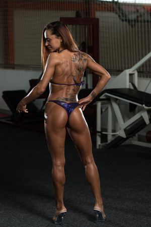 Portrait Of A Young Physically Fit Woman Showing Her Well Trained Body - Muscular Athletic Bodybuilder Fitness Model Posing After Exercises Stock Photo