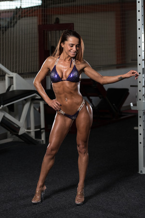 physically fit: Portrait Of A Young Physically Fit Woman Showing Her Well Trained Body - Muscular Athletic Bodybuilder Fitness Model Posing After Exercises Stock Photo