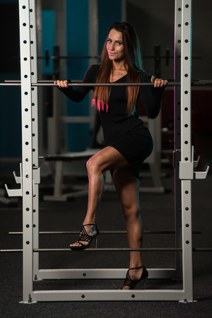 gym dress: Beautiful Young Woman With Long Hair In A Black Skirt Posing In Gym - Squat Cage Stock Photo