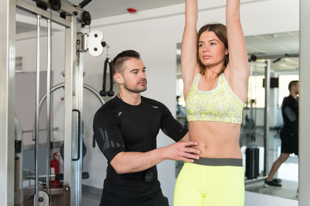 abdominals: Personal Trainer Showing Young Woman How To Train On Abs Abdominals In The Gym