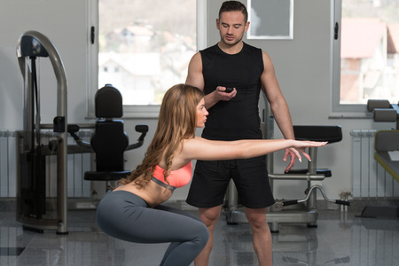 balance ball: Personal Trainer Showing Young Woman How To Train On Bosu Balance Ball In A Gym Stock Photo