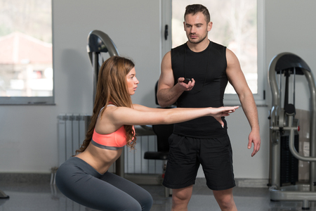 balance ball: Personal Trainer Showing Young Woman How To Train On Bosu Balance Ball In A Health And Fitness Concept Stock Photo