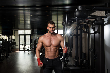fitness hombres: Retrato de un hombre físicamente ajuste que presenta en Modern Centro Fitness Gimnasio