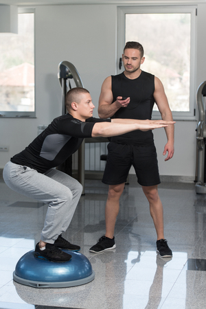 balance ball: Personal Trainer Showing Young Man How To Train On Bosu Balance Ball In A Gym