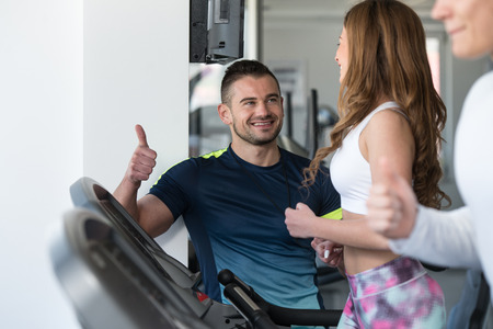 eliptica: Personal Trainer Showing Ok Sign To Client - Group Of People Exercising On Elliptical Walker In Gym Or Fitness Club