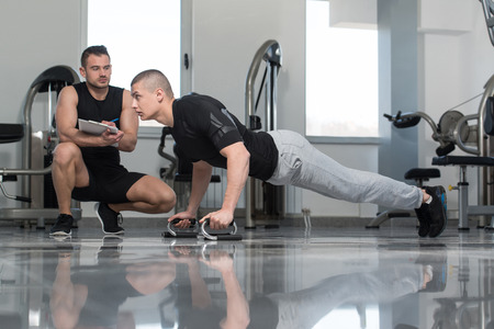 pushup: Personal Trainer Showing Young Man How To xercise Push-Up Strength In A Health And Fitness Concept Stock Photo