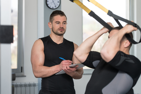 Personal Trainer Working With A Young Man At The Gym Writing Notes On A Clipboard In A Health And Fitness Concept