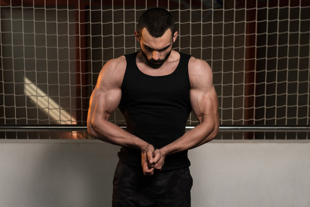 only the biceps: Portrait Of A Young Fit Man Showing His Well Trained Body In Tank - Muscular Athletic Bodybuilder Fitness Model Posing After Exercises
