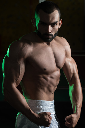 only the biceps: Portrait Of A Young Fit Man Showing His Well Trained Body - Muscular Athletic Bodybuilder Fitness Model Posing After Exercises