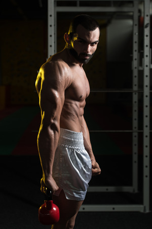 Young Man Working With Kettle Bell In Gym Stock Photo