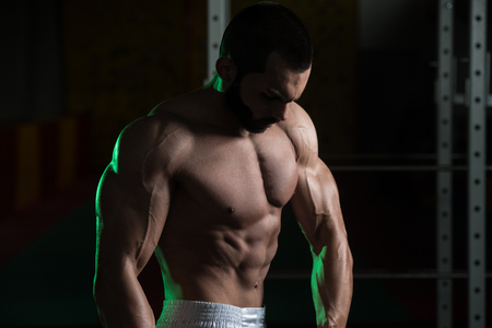 only the biceps: Young Man Standing Strong In The Gym And Flexing Muscles - Muscular Athletic Bodybuilder Fitness Model Posing After Exercises Stock Photo