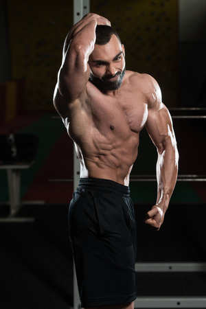 only the biceps: Young Man Standing Strong In The Gym And Flexing Muscles - Muscular Athletic Bodybuilder Fitness Model Posing Showing Abs After Exercises