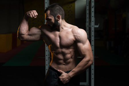 only the biceps: Young Man Standing Strong In The Gym And Flexing Front Double Biceps Pose - Muscular Athletic Bodybuilder Fitness Model Posing Exercises