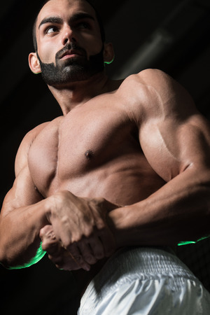 physically fit: Portrait Of A Young Physically Fit Man Performing Side Chest Pose - Muscular Athletic Bodybuilder Fitness Model Posing After Exercises Stock Photo