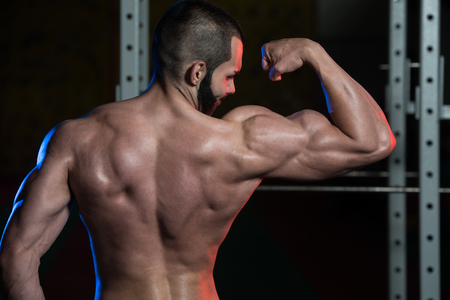 only the biceps: Portrait Of A Young Fit Man Flexing Front Biceps Pose - Muscular Athletic Bodybuilder Fitness Model Posing After Exercises