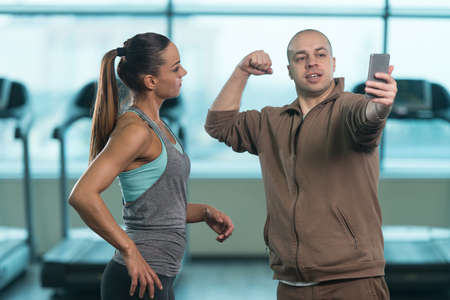 bald: Bald Guy Showing Prety Young Woman How To Take A Selfie With A Cellphone In Fitness Center - Gym In The Background Stock Photo