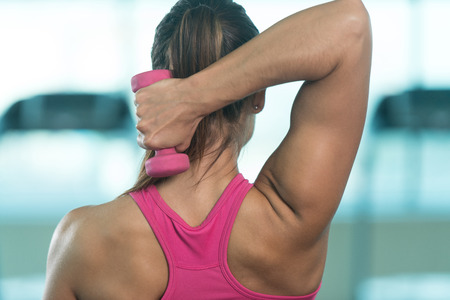 Healthy Fitness Woman Working Out Triceps With Dumbbell In A Gym Stock Photo