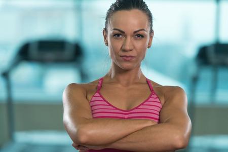 Retrato de una mujer joven físicamente ajustada mostrando su cuerpo bien entrenado - atlética muscular del Bodybuilder modelo de la aptitud que presenta después de ejercicios Foto de archivo
