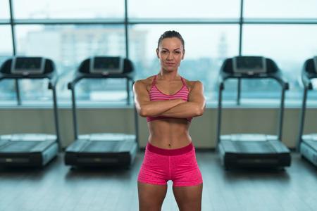 Porträt eines jungen Körperlich fit Frau sie gut trainierter Körper angezeigt - Muskulöser athletischer Bodybuilder Fitness Model Posing nach Übungen Standard-Bild