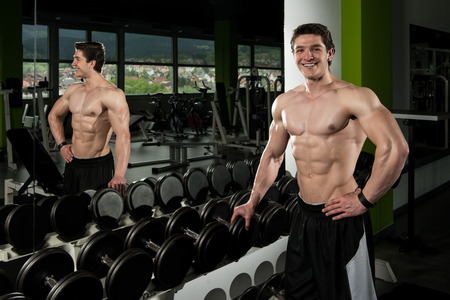 straining: Bodybuilder Standing Strong Next To The Mirror  - Male Showing Muscles Straining - Beautiful Muscular Body Athlete Stock Photo