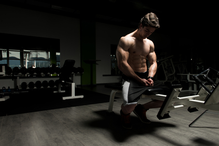 muscular body: Good Looking And Attractive Young Man With Muscular Body Sitting On Bench And Relaxing In Gym