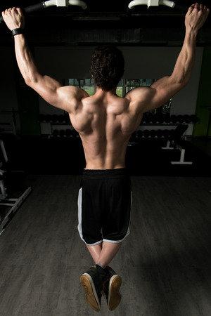 strong chin: Young Man Athlete Doing Pull Ups - Chin-Ups In The Gym Stock Photo
