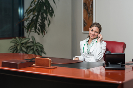 healthcare worker: Beautiful Young Female Doctor Woman In office Talking On Cell Phone - Healthcare Worker Working Online