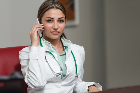 healthcare worker: Indoor Portrait Of A Beautiful Happy Brunette Female Doctor Talking On Her Cell Phone - Healthcare Worker Working Online