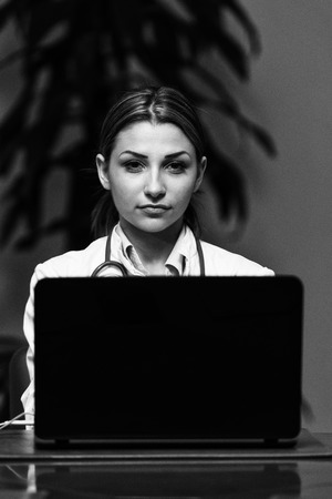healthcare worker: Portrait Of A Young Female Doctor Using Laptop At Office - Healthcare Worker Working Online Stock Photo