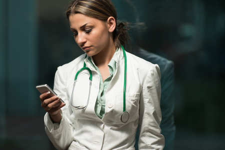 healthcare worker: Beautiful Female Doctor Working Taking Notes On Mobile - Healthcare Worker Working Online