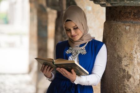 koran: Humble Muslim Woman Is Reading The Koran Outdoors Stock Photo