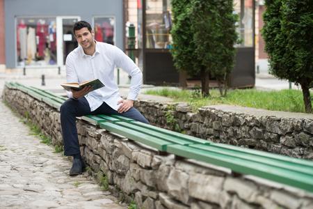koran: Adult Muslim Man Is Reading The Koran Outdoors