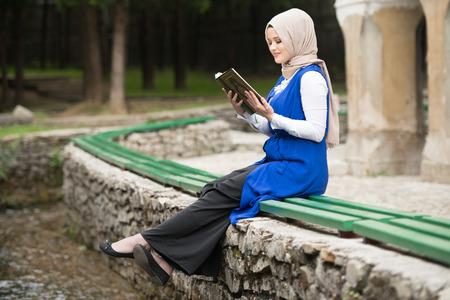 Humble Muslim Woman Is Reading The Koran Outdoors Stock Photo