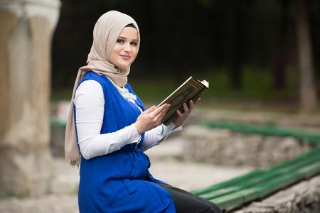 humilde: Mujer musulmana humilde está leyendo el Corán al aire libre