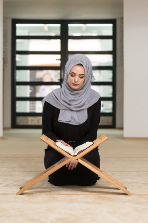 Beautiful Muslim Woman Wearing Hijab And Reading The Koran Stock Photo