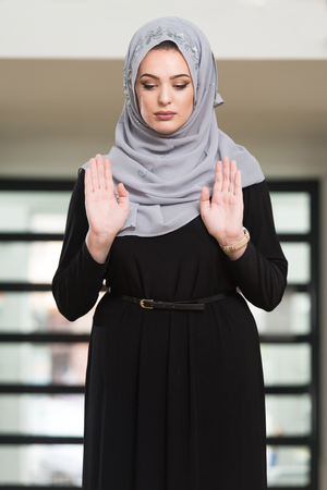 Young Muslim Woman Making Traditional Prayer To God While Wearing A Traditional Hijab And Dress Stock Photo
