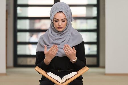 Muslim Woman Reading Koran Or Quran Wearing Traditional Dress At The Mosque